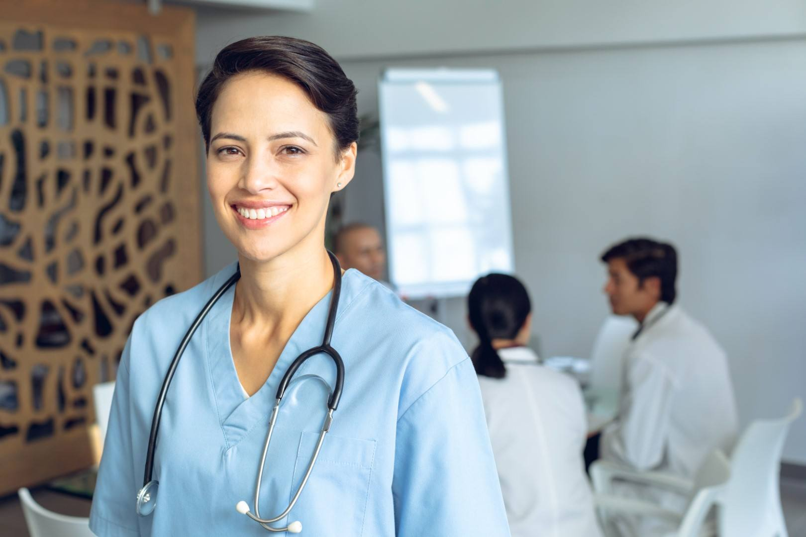Front view of happy female Caucasian nurse looking at camera in conference room in hospital. Diverse colleagues in meeting sitting at the table of conference room in background.