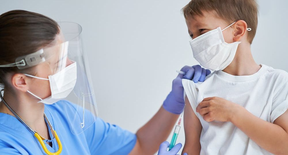 Boy getting vaccinated at health clinic