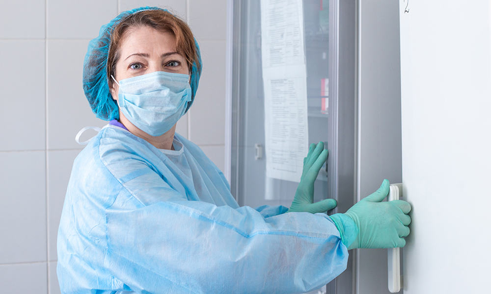 Health care worker accessing vaccine storage unit